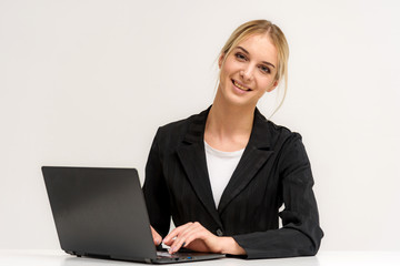 Studio photo of a beautiful blonde girl is talking on a white background sitting at a table with a laptop.
