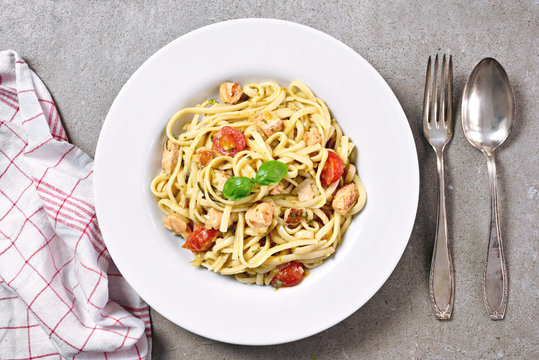 Delicious salmon pasta dish, tagliatelle or linguine noodles. High angle view of fresh spaghetti pasta with herbs and cherry tomatoes.