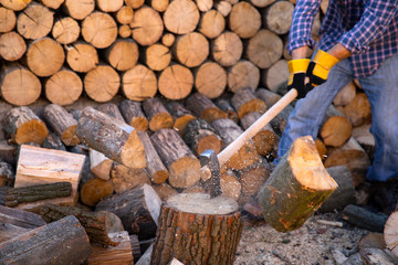 Man holding an industrial ax. Ax in hand. A strong man holds an ax in his hands against the background of chainsaws and firewood. Strong man lumberjack with an ax in his hand. Chainsaw close up.