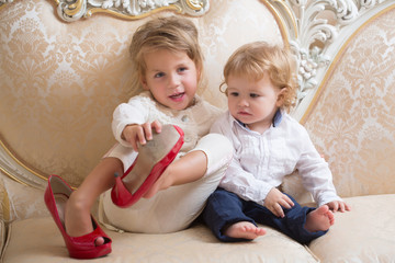 Girl and boy with blond hair sit on classic sofa