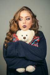 Beauty salon and hairdresser. fashion girl with glamour makeup hold toy bear. woman with makeup and long curly hair. Makeup cosmetics and skincare. Fashion portrait of woman. Glamour fashion model