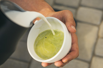 relax in cafe or coffee shop and drinking. matcha latte tea ceremony, pour milk. perfect morning with green coffee. barista pour milk in japanese tea drink. Enjoying beautiful morning. Good morning