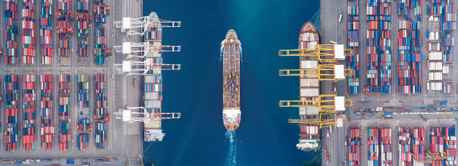 Aerial view panoramic oil tanker moving pass sea port warehouse and container ship.