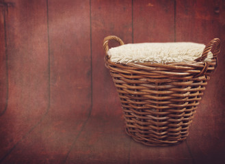 Wicker basket against a brown wooden floor