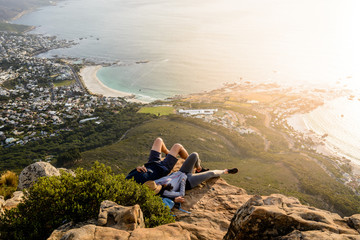 A couple is relaxing on top of Lion's Head mountain in Cape Town and enjoying the beautiful sunset with a view of Camps Bay and Clifton Beach areas