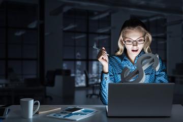 Attractive blonde wearing glasses in dark office using laptop. M