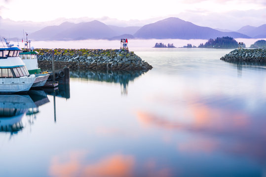 seascape sitka alaska, waterfront reflected sunrise colors on water. a coastal village with fishing and cruise vessels, mountains and sea smoke in background
