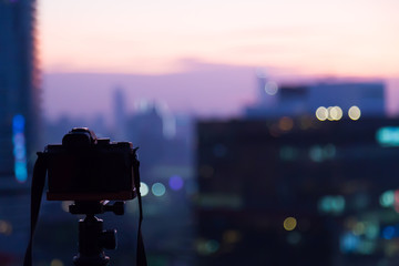 Silhouette of camera in front of dusk sky and Bangkok city scape.