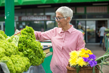 Senior woman holds basket with flowers and  buys lettuce on market