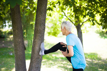 Senior woman does stretching exercise in the park