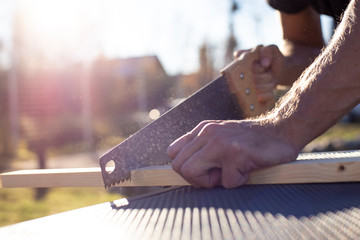 A man cuts a wooden product with a carpentry hand saw, in the sunshine on a warm summer day, outdoors.