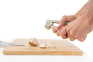 Male hand pressing garlic masher isolated on white background.