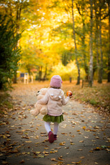 Little girl playing in Autumn park, walk with apple and plush bear