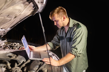Mechanic in uniform looking intently at the laptop is connected to the motor vehicle for testing and adjustment. Mechanic carries out maintenance of the car. The removal of bugs of the engine.