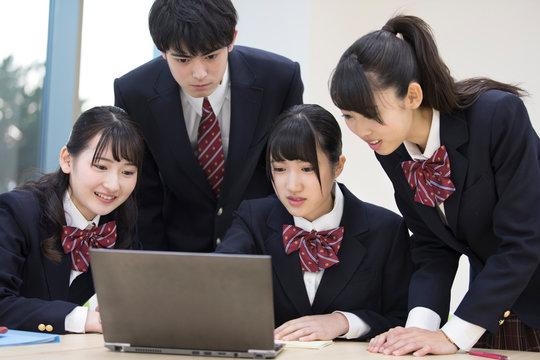 集まってパソコンを見る高校生たち