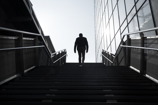 avenir silhouette homme marche escalier avancer perspective demain travailler projet construire seul solitude aide aider marcher monter gravir effort immeuble façade moderne building dos