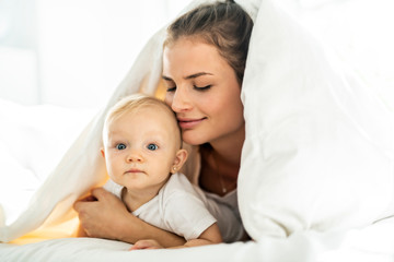 Portrait of young mother with infant baby girl liying on the bed covered with a white blanket