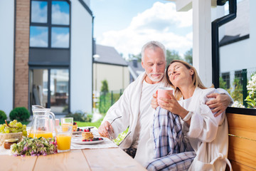 Real relief. Appealing wife feeling relived and relaxed while enjoying her morning with her handsome bearded husband Wall mural