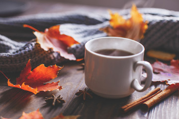 Türaufkleber Kaffee Coffee mug with autumn maple leaves and women's woolen scarf on a wooden table