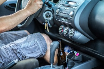 Man drinking alcohol while driving a car