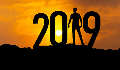 man on mountain is greeting 2019 with power and confidence