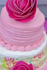 Close up of a party cake with pink flower decorations and frosting