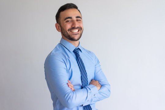 Portrait of joyful professional. Young business man blue shirt and tie crossing arms and smiling at camera. Successful businessman concept