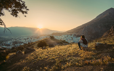 man sitting on top of the mountain enjoying the beautiful view during a vibrant sunset. Chefchaouen panorama, blue city skyline on the hill, Morocco