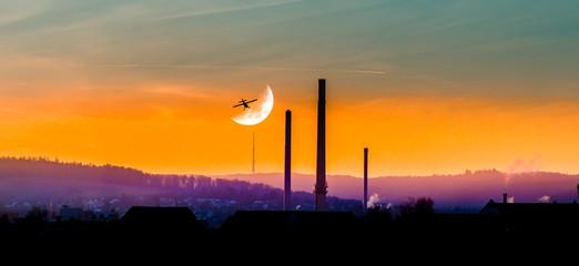 Flugzeug fliegt über der Stadt dem Mond entgegen