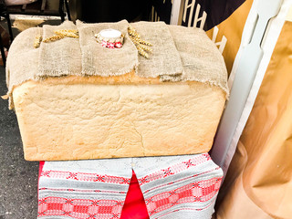 A large, huge rectangular loaf of white homemade, homemade wheat bread with a crust and salt. Russian tradition to meet guests. bread made by female hands