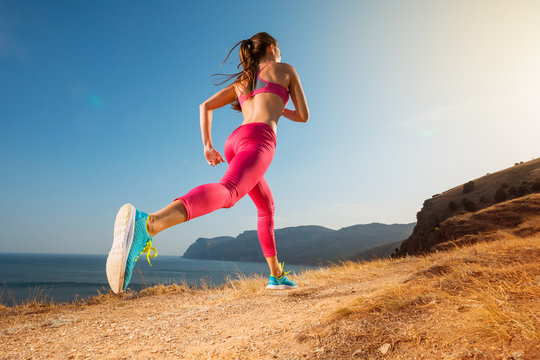 Woman running. Young girl runner jogging on a mountain trail in the beautiful landscape. Healthy sport lifestyle. Fitness and workout on outdoors