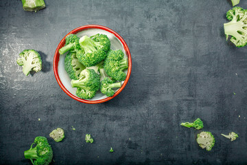 Fresh raw broccoli in a wooden bowl on a dark background.Top view. Free space.