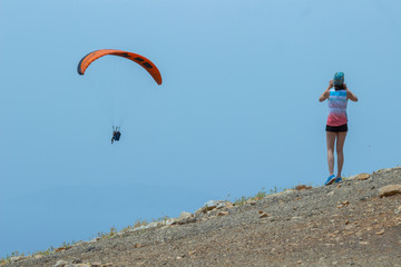 A girl takes a picture of people flying on a parachute. Edge of the mountain, blue sky
