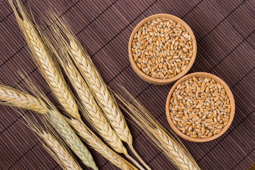 Wheat grains and spikelets of wheat on a brown background. Top view