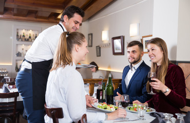 Handsome waiter serving meals to friendly company