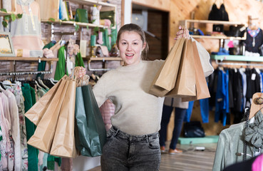 Young woman is standing satisfied after shopping