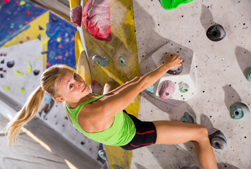 Female practicing indoor rock-climbing