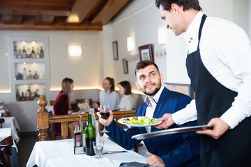 Waiter serving delicious salads to handsome young man at restaurant