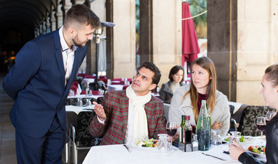 Angry guests with manager in restaurant