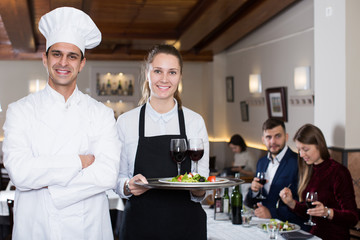 Portrait of confident male chef and smiling waitress