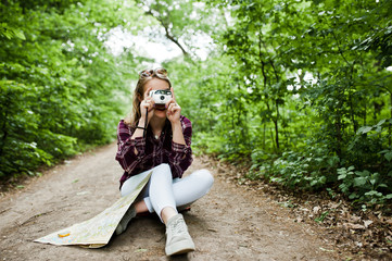 Portrait of an attractive blond girl with a map sitting in the forest and taking photos.