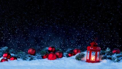 Laterne mit Weihnachtskugeln und Tannenzweig vor dunklem Hinterdrund mit Schnee Wall mural