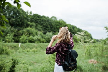 Portrait of an attractive blond girl in tartan shirt with backpack walking in the countryside.