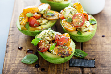 Avocado stuffed with pesto caprese salad