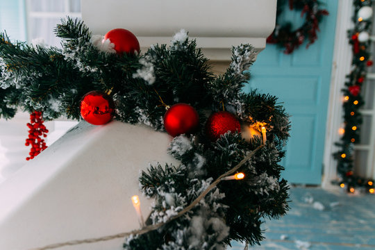 Winter wreath hanging on a door of house decorated by Christmas pine branch with red baubles and decorative snow.