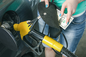 Expensive gasoline. Lack of money for gasoline and fuel. Driver holds one dollar end empty wallet on background of a fuel nozzle in the gas tank. Increase in gasoline prices concept.