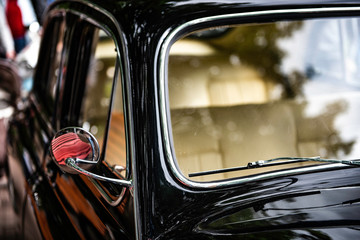 old black classical car. side view. the chromeplated mirror. sunshine