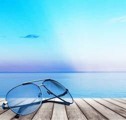 Sunglasses on sandy beach background