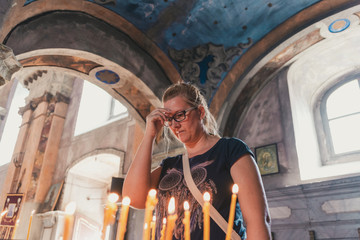 woman lights candles in church