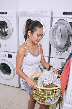 Young Asian university student unloading washing machine